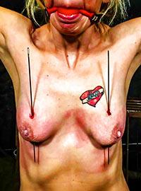 Insertion of long needles into flesh of blonde girl loving pain
