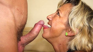 Mature woman's tongue stroked over the head of her young lover's cock